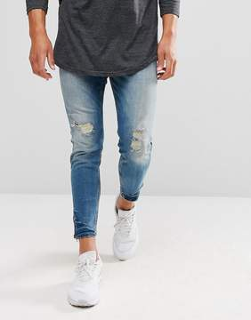 Pull&Bear Carrot Fit Ripped Jeans With Zipped Hem In Mid Wash