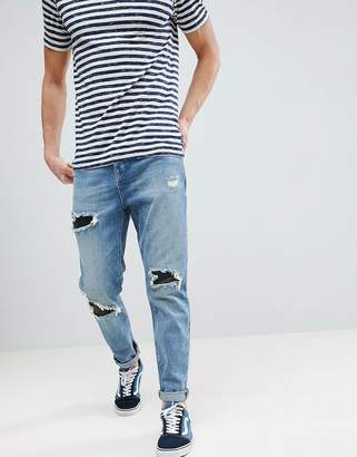 Asos DESIGN Tapered Jeans In Mid Wash Vintage With Faux Leather Rip & Repair