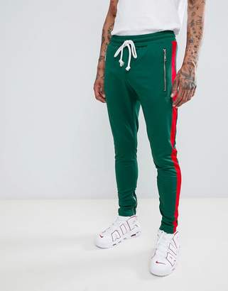 Criminal Damage skinny joggers in green with red side stripe