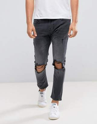 Bershka Skinny Tapered Jeans With Knee Rip In Washed Black