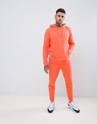 Asos DESIGN tracksuit hoodie / skinny joggers in orange