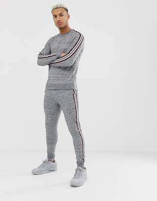 Asos Design DESIGN tracksuit sweatshirt/skinny joggers in grey and navy interest fabric with side stripe