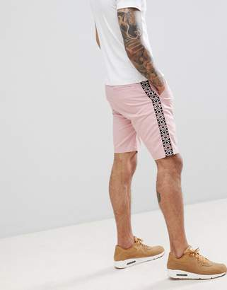 Asos DESIGN slim shorts in pastel pink with geo-tribal side tape