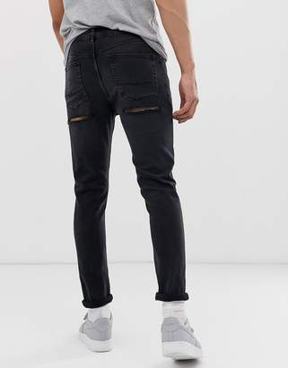 Asos Design DESIGN skinny jeans in washed black with bum rips