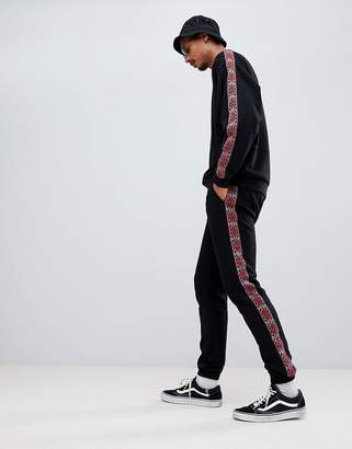 Asos DESIGN skinny joggers with geo-tribal side stripe