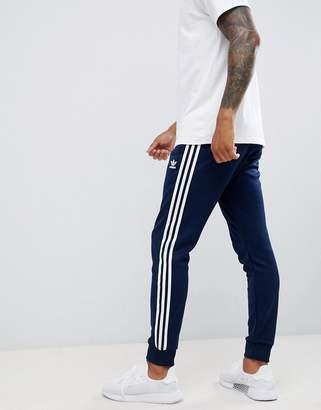 adidas 3-stripe skinny joggers with cuffed hem in navy DH5834