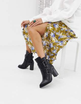 Glamorous black pointed heeled ankle boots with buckles