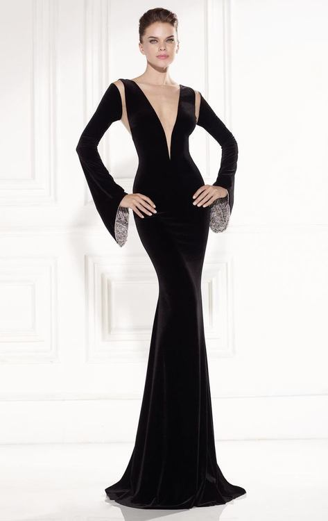 Walk in seduction and style in this gown by Tarik Ediz 92519. The exclusive bodice has illusion details and long belled sleeves with a iridescent crystal lining. This elegant style creates a sultry plunging effect that will boast your curves to the full-length hem for a fantastic and unforgettable black tie or red carpet ensemble. Make it a romantic occasion with this gown by Tarik Ediz. Model is wearing Black color.