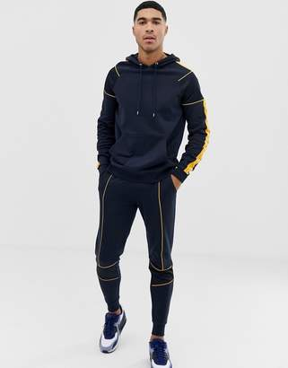 Asos Design DESIGN tracksuit hoodie/skinny sweatpants with piping and mesh panels in navy