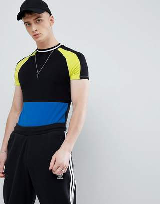 Asos DESIGN muscle fit raglan t-shirt with contrast color block and tipping in black