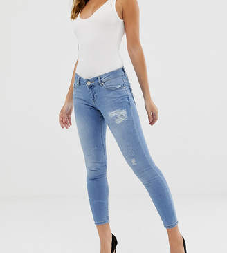 Asos DESIGN Petite Whitby low rise skinny jeans in mid wash blue with rip and repair