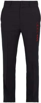 Arrow-embroidered slim-leg wool trousers