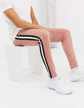 Asos Design DESIGN skinny joggers in poly tricot with side stripe in pink