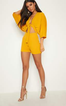 3197ab4d6deb at PrettyLittleThing · PrettyLittleThing Mustard Crepe Batwing Cut Out  Playsuit