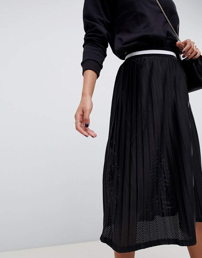 – Mit Löchern verzierter, halblanger Faltenrock mit sportlich gestreiftem Bund