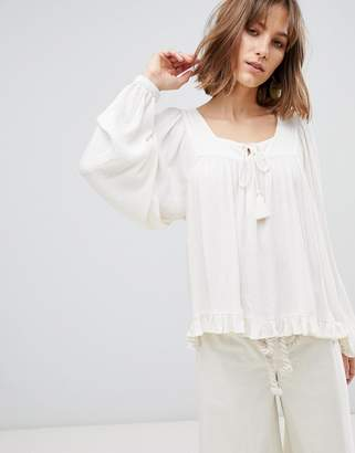 Asos Design DESIGN smock long sleeve top with tassel ties in textured fabric