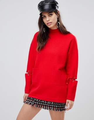 Liquorish long sweater with front pockets and lacing detail on sleeves