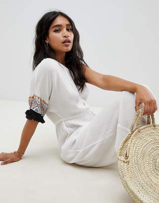 Asos Design DESIGN embroidered fringed tape one shoulder beach jumpsuit in white