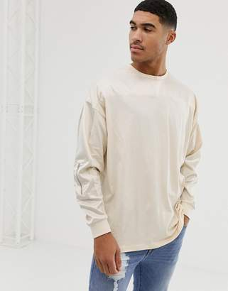 BEIGE Asos Design ASOS DESIGN oversized longline long sleeve t-shirt with contrast woven fabric yoke and sleeve with zip pocket in