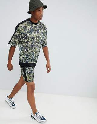 Asos Design DESIGN tracksuit oversized sweatshirt/skinny shorts in mesh digital camo with side stripe