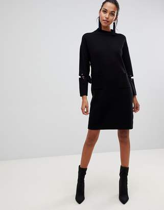 Liquorish long jumper dress with front pockets and lacing detail on sleeves
