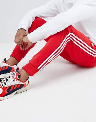 adidas 3-stripe skinny joggers with cuffed hem in red DH5837