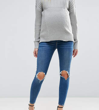 Asos DESIGN Maternity Ridley skinny jeans in roy dark stonewash with busted knees with under the bump waistband