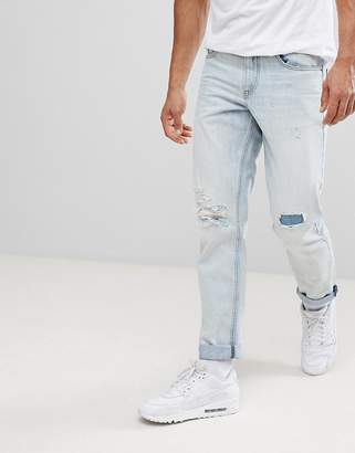 Asos DESIGN Slim Jeans In Bleach Wash With Rip And Repair