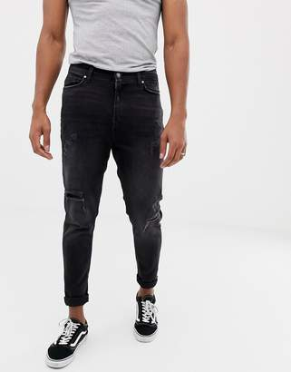 Bershka carrot fit jeans in black with rips and hem taping