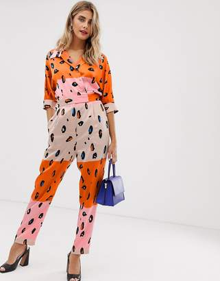 Liquorish jumpsuit with belt in contrasting orange leopard print