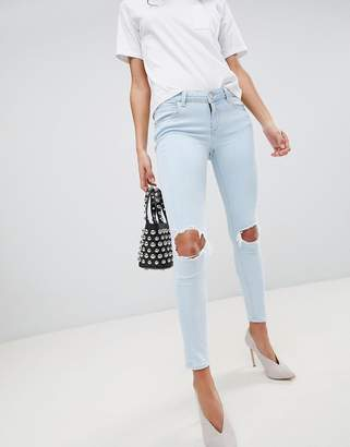 Asos DESIGN Whitby low rise skinny jeans in philomena light ice stone wash with busted knees