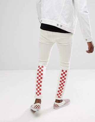 Asos DESIGN super skinny jeans in white with red checkerboard print