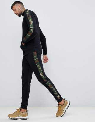Asos DESIGN tracksuit jersey track jacket/skinny joggers with camo side stripe