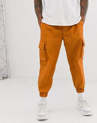 Asos tapered sweatpants in rust nylon with cargo pockets