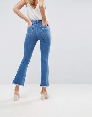 Asos DESIGN Egerton rigid cropped flare jeans in mid wash blue with raw hem