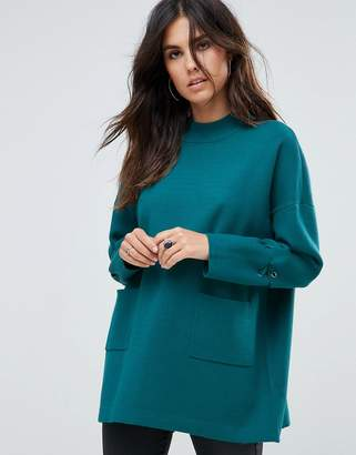 Liquorish Long Turtleneck Sweater With Front Pockets And Lacing Detail On Sleeves