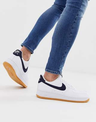 Nike Force 1 trainers with navy swoosh and gum sole
