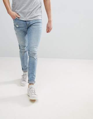 Asos DESIGN Super Skinny Jeans In Light Wash Blue With Abrasions