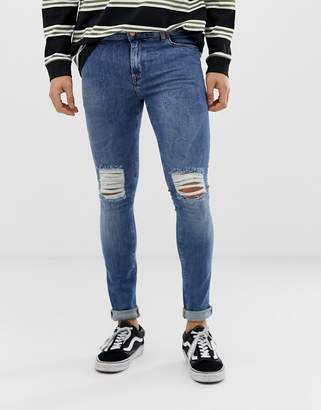 Asos DESIGN super skinny jeans in 12.5oz mid wash blue with knee rips