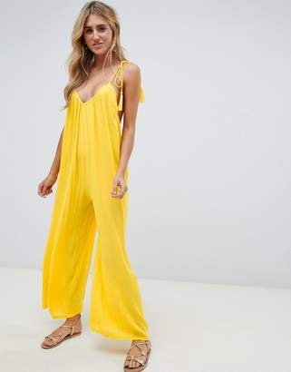 Asos Design DESIGN crinkle low back beach jumpsuit with tassel ties in yellow