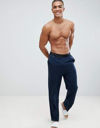 Asos DESIGN straight leg jersey pyjama bottom in navy with branded waistband in organic cotton