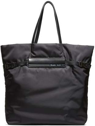 Prada Trimmed Tote From Black Trimmed Tote With Top Handle, Compression Tab On Sides, Top Zip Closure, Internal Compartment And Front Logo Patch.