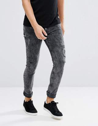 Asos Design Super Skinny Jeans In Vintage Washed Black With Rip And Repair