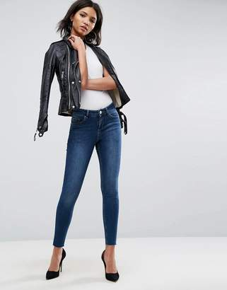 Asos DESIGN Lisbon midrise skinny jeans in kyla wash with raw hem