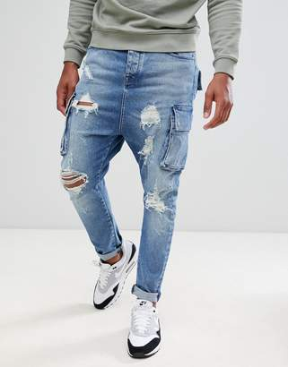 Asos DESIGN drop crotch jeans in mid wash blue with cargo pockets and rips