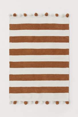 H&M Cotton rug with pompoms