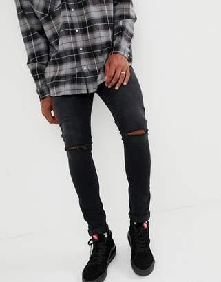Asos DESIGN 12.5oz super skinny jeans in black with knee rips