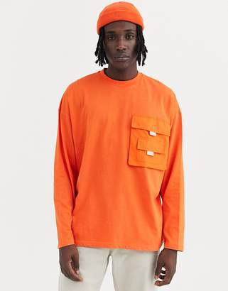 Asos Design DESIGN oversized long sleeve t-shirt with woven utility pocket in orange