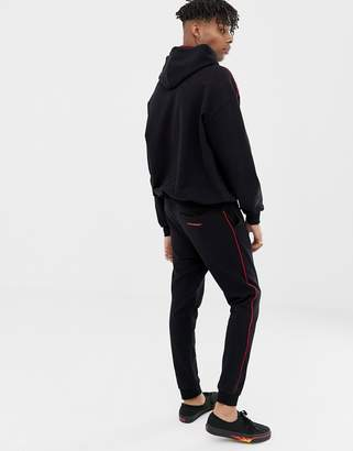 Cheap Monday jogger bottoms in black with red stripe