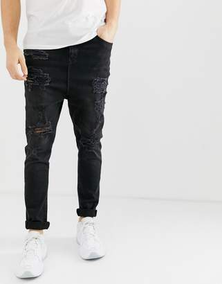 Asos DESIGN drop crotch jeans in washed black with abrasions